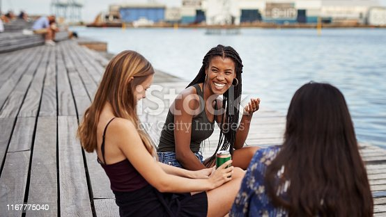 Cropped shot of three attractive young friends sitting on the deck together and bonding during a day by the canal