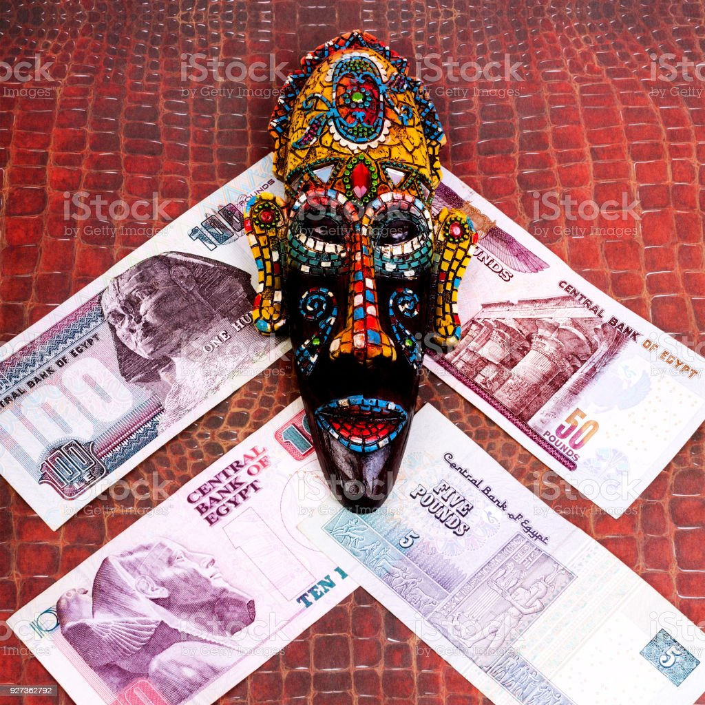 The Egyptian souvenir mask and the Egyptian money, on a red background of crocodile skin. Square. The Egyptian souvenir mask and the Egyptian money, on a red background of crocodile skin. Square. Close-up. Africa Stock Photo