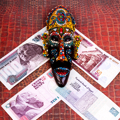 The Egyptian Souvenir Mask And The Egyptian Money On A Red Background Of Crocodile Skin Square Stock Photo - Download Image Now