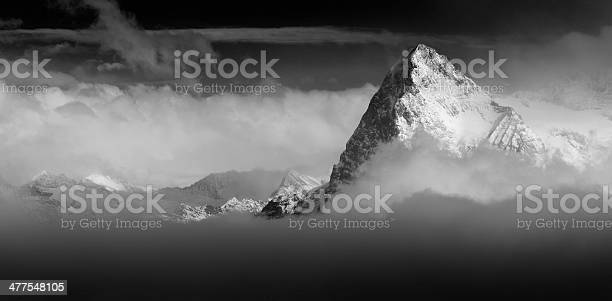 Photo of The Eiger North Face Switzerland Alps rising above the clouds