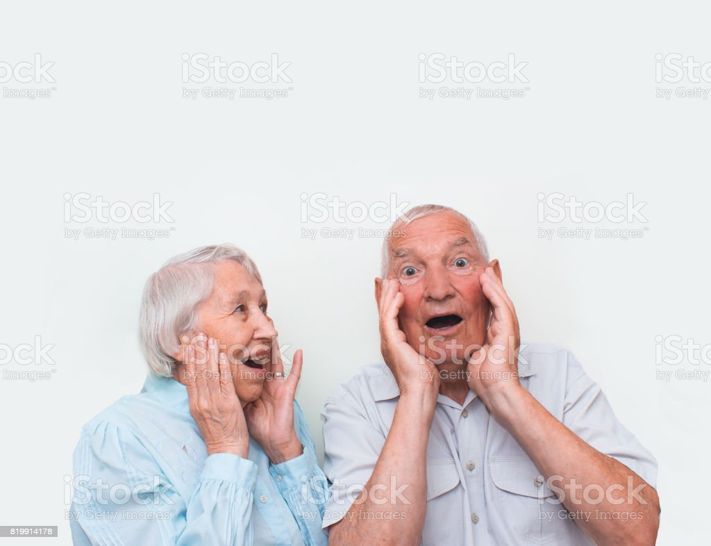 The elderly couple surprised by raising both hands stock photo