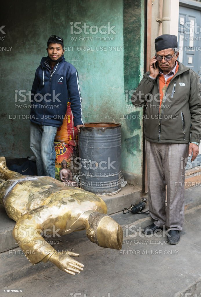 The elderly Nepalese beside  his the bronze sculpture. stock photo