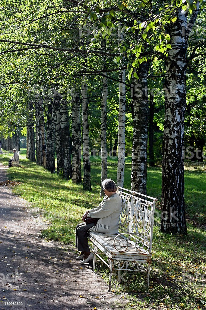The elderly woman on a bench in park stock photo