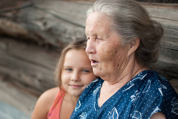 The elderly woman with grand daughter stock photo
