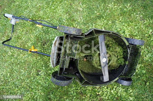 istock The electric lawn mower lies on the grass upside down with wheels 1049658454