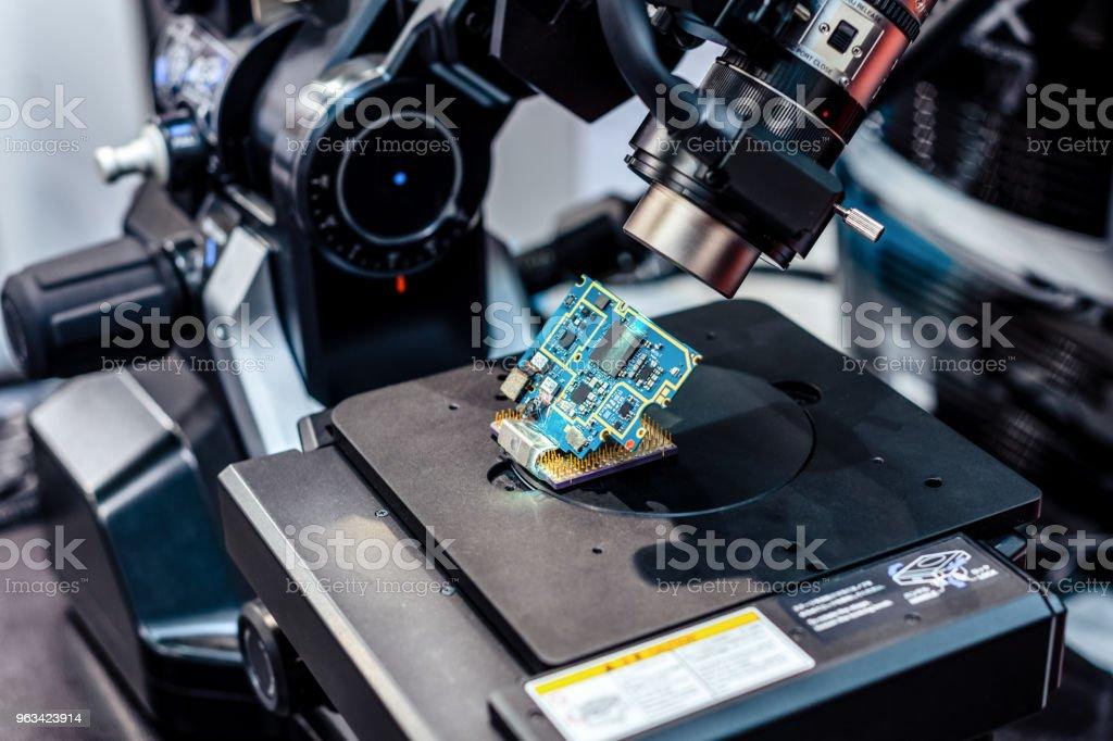 La carte électronique est vérifiée à l'aide d'un microscope électronique - Photo de Analyser libre de droits