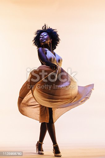 The elegant dancer, Portrait of a beautiful woman swirling her dress, isolated on beige studio background