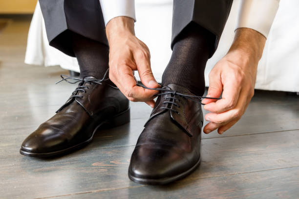 The elegant man laces shoes stock photo