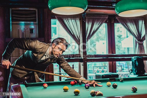 A beautifully dressed young man plays billiards in a pub and drinks beer