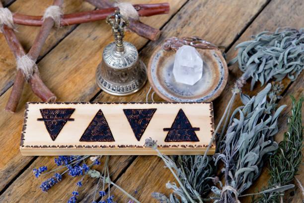the elements - earth, fire, water, air with brass bell, quartz crystal, branch pentagram and bundles of dried herbs - традиционная церемония стоковые фото и изображения