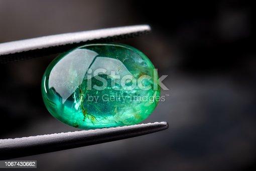 The emerald gemstone jewelry photo with dark lighting background.
