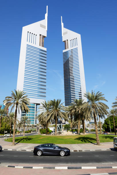 The Emirates Towers and Tesla Model S electric car Dubai, UAE - November 19, 2017: The Emirates Towers and Tesla Model S electric car. The Emirates Towers complex is set in over 570,000 m2 tesla model s stock pictures, royalty-free photos & images
