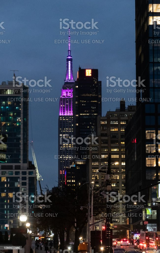 The Empire state building lit in Purple seen between other skyscrapers As seen from 12th Avenue stock photo
