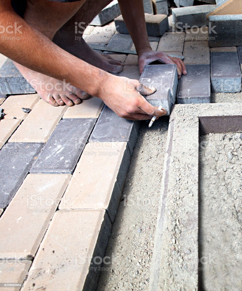 The employee puts the paving slab on the sidewalk stock photo