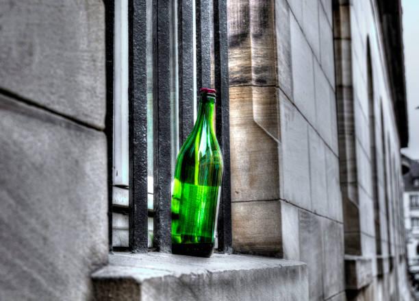 die leere flasche aus grünem glas kosten auf einem fensterbrett auf der straße - kinderlieder frühling stock-fotos und bilder