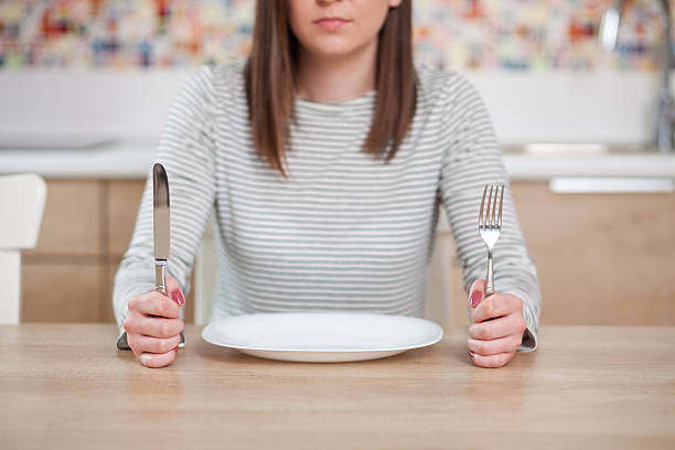 The empty plate Displeased young woman sitting at the empty plate. Shallow depth of field, focus on foreground hungry stock pictures, royalty-free photos & images