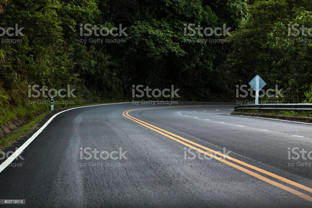 The empty road is surrounded by forests on either side. stock photo