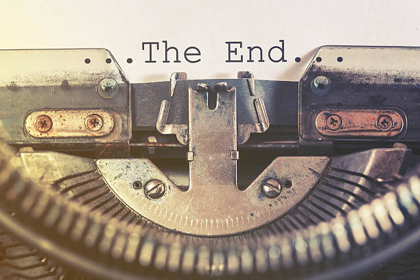 the end message written on a vintage typewriter - finishing stock photos and pictures