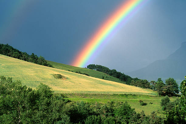 The end of a rainbow with a field in the foreground stock photo