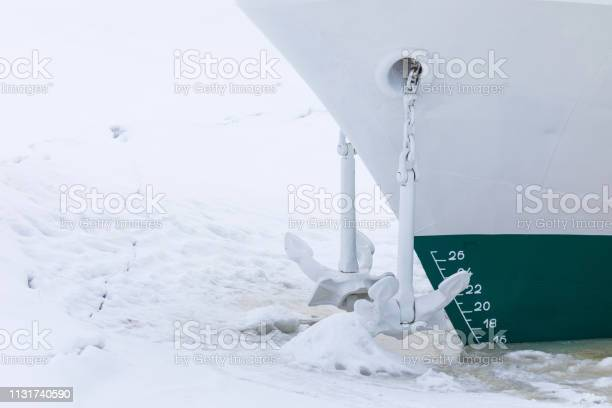 Photo of The end of navigation. The ship or vessel is in the captivity of ice and snow. Its anchor in the front part hangs in the air. The winter landscape of the river or the lake in the cold sunny day.