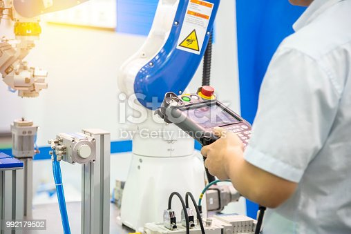 874298574 istock photo The engineer control the robotic arm for manufacturing process. 992179502
