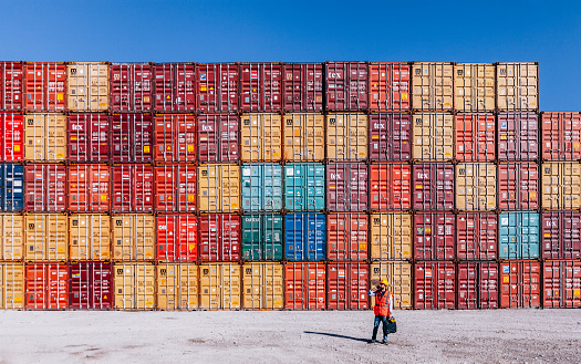 Engineer man with yellow crash helmet and worker west talkig with smartphone and checking cargo freights in front of colorful cargo container stacks in shipping port