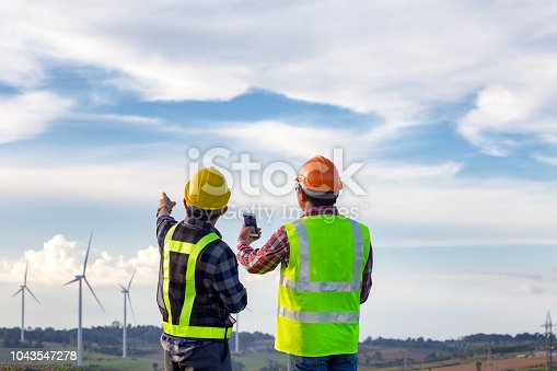The engineers standing outdoor survey wind turbines green energy  together and analysis energy of wind turbine construction this is electric energy.
