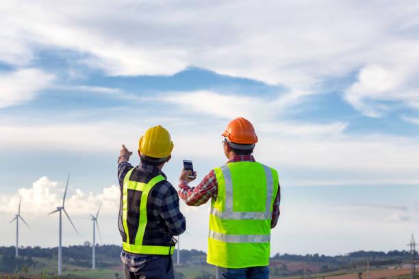 the engineers standing outdoor survey wind turbines green energy  together - potęga w naturze zdjęcia i obrazy z banku zdjęć