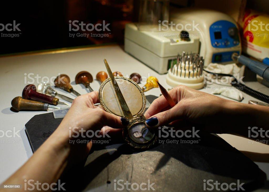 O gravador coloca uma marcação na medalha sobre o colar. - Foto de stock de Antigo royalty-free