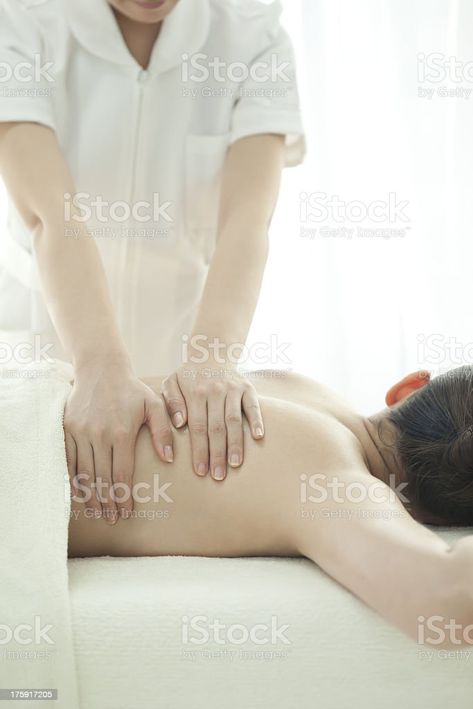 The esthetician who massages a back royalty-free stock photo