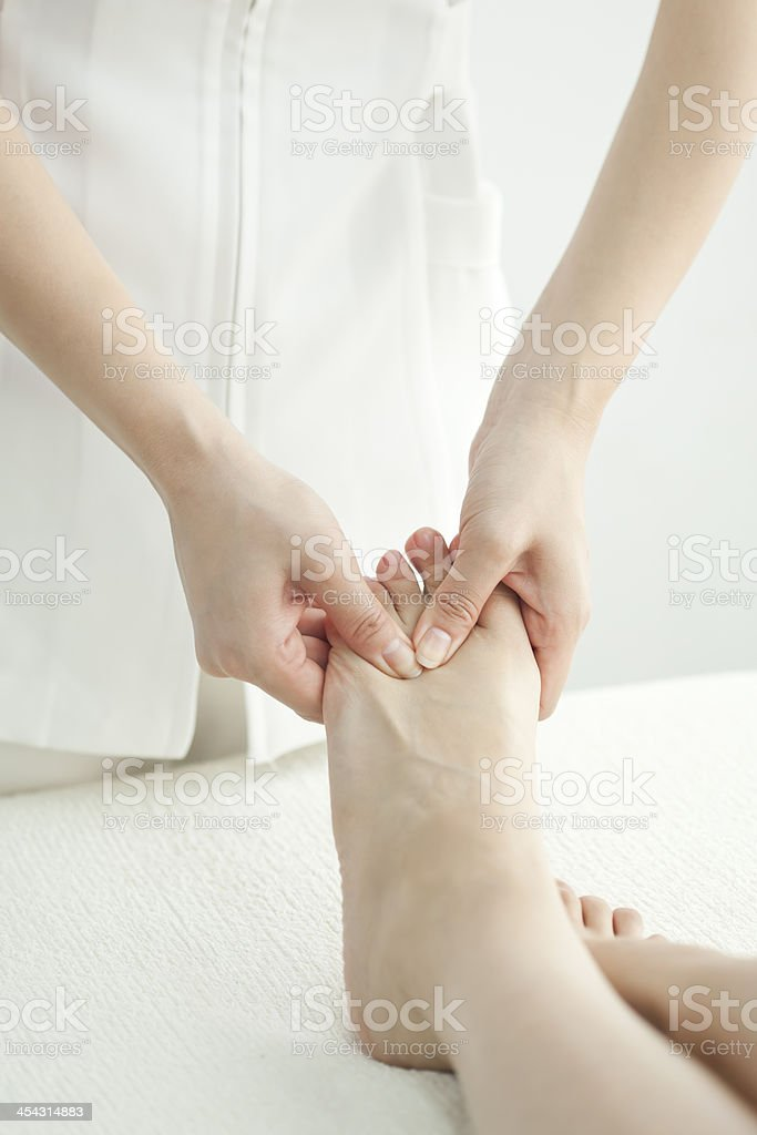 The esthetician who massages a foot royalty-free stock photo