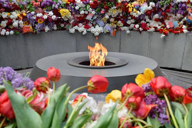 The eternal flame at Tsitsernakaberd, Yerevan, Armenia Tsitsernakaberd, The Armenian Genocide memorial complex. The eternal flame at the center of the twelve slabs. Yerevan, Armenia genocide stock pictures, royalty-free photos & images