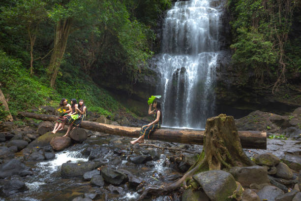 the ethnic minority girls are having relaxing beside waterfall - minority stock photos and pictures
