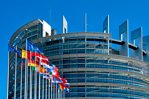 The European Parliament building in Strasbourg, France with flags waving calmly celebrating peace of the Europe. July 12, 2020.