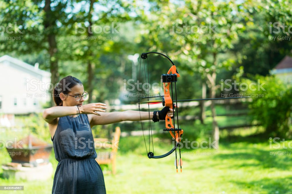 The teenager girl practicing archery at the backyard of the country...