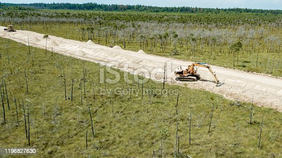 The excavator works on the consruction of the road through the swamp Olmany. Ecological problem.
