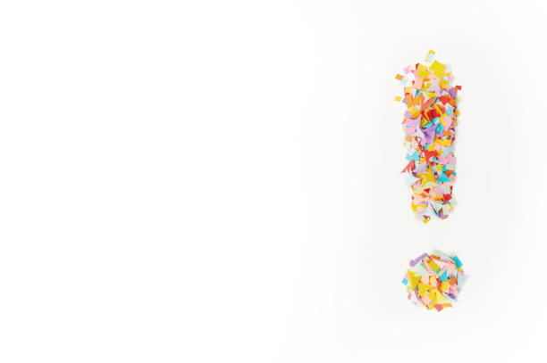 The exclamation mark on a  background from multi-colored confetti, from pieces of color paper. stock photo
