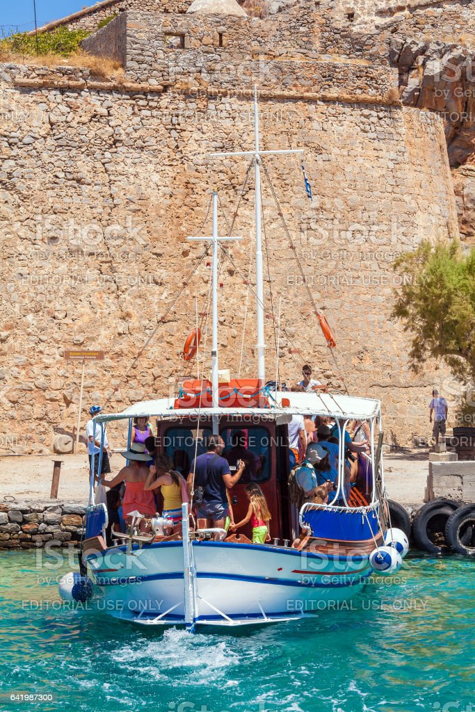 SPINALONGA, GREECE - JULY 31, 2012:  The excursion boat took a group of tourists to visit  Spinalonga stock photo