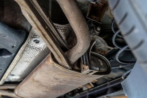 Die Auspuffanlage im Auto von unten gesehen, das Auto steht auf dem Lift in der Autowerkstatt. – Foto