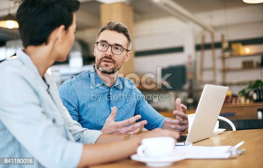 Shot of a man and woman going through paperwork and using a laptop together in their coffee shop