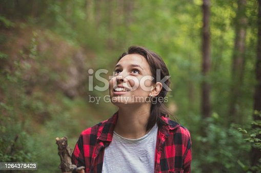 An image of a beautiful young woman during her adventure in remote woods. She can't help but stop and stare every 10 steps.
