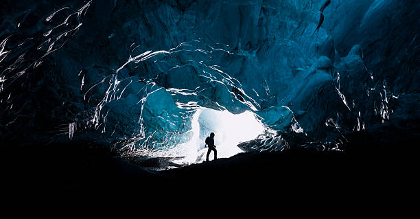 The explorer Man exploring an amazing glacial cave in Iceland explorer stock pictures, royalty-free photos & images