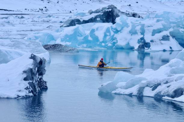 The Explorer An extreme adventurer paddles out on Jokulsarlon Lagoon in winter in Iceland at -20C. jokulsarlon stock pictures, royalty-free photos & images