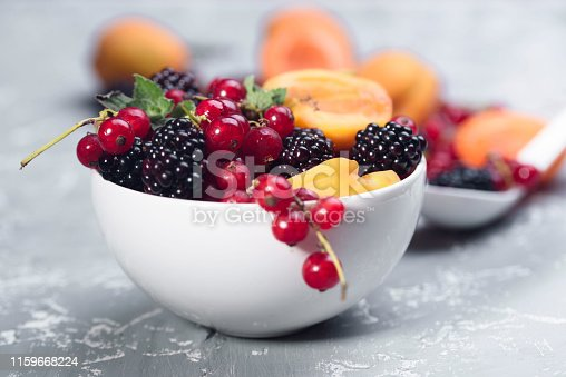 502634476istockphoto The explosion of different berries. Photo, red currant, black currant, blackberry, apricot on a concrete background. 1159668224