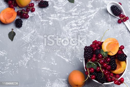 502634476istockphoto The explosion of different berries. Photo, red currant, black currant, blackberry, apricot on a concrete background. 1159668226