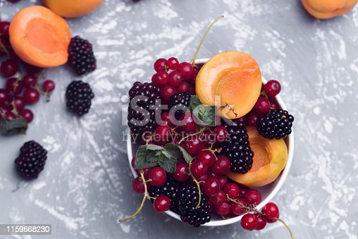 502634476istockphoto The explosion of different berries. Photo, red currant, black currant, blackberry, apricot on a concrete background. 1159668230