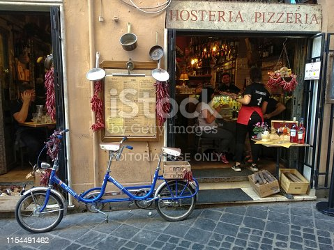 The exterior of a pizzeria in Rome, Italy, is captured on an autumn day. There is a blue bike parked in front of the pizzeria. In Rome, especially in the tourist spots, there are a lot of pizzerias, taverns, and inns. They are usually located downtown, in old buildings and have antique interior and old-fashioned exterior design.