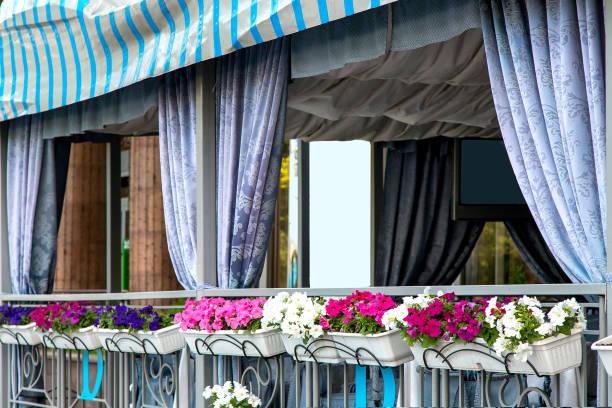 das äußere des restaurants ist mit tuch und blumentöpfe mit blumen geschmückt. - garagen pergola stock-fotos und bilder