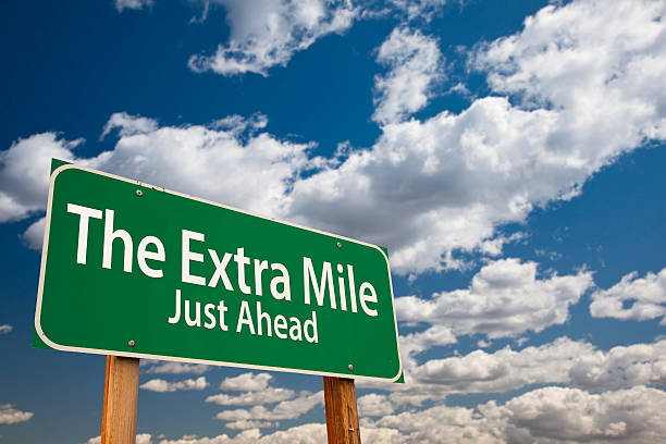 The Extra Mile Just Ahead Green Road Sign Over Sky The Extra Mile Just Ahead Green Road Sign Over Dramatic Clouds and Sky. dedicated stock pictures, royalty-free photos & images
