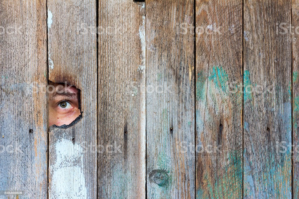 the eyes of a man spying through a hole stock photo